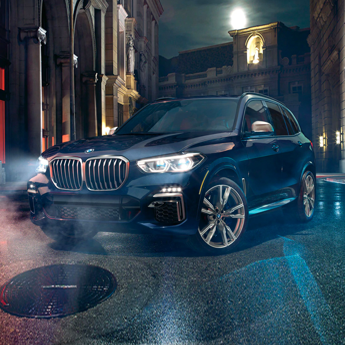Profile view of blue 2021 BMW X5 at night